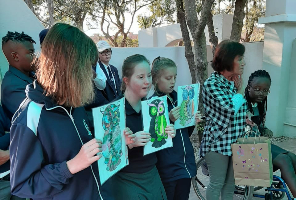 Colouring in competition winners holding their pictures of owls