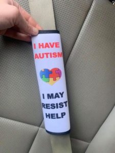 Seatbelt cover with message about autism